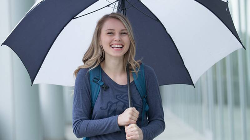 student holding umbrella