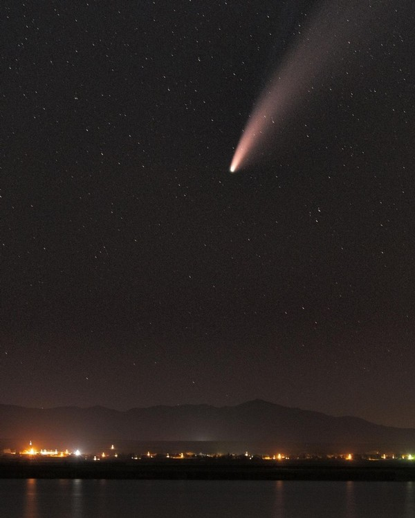 The NEOWISE comet streaks through the sky above the Benson Marina at night