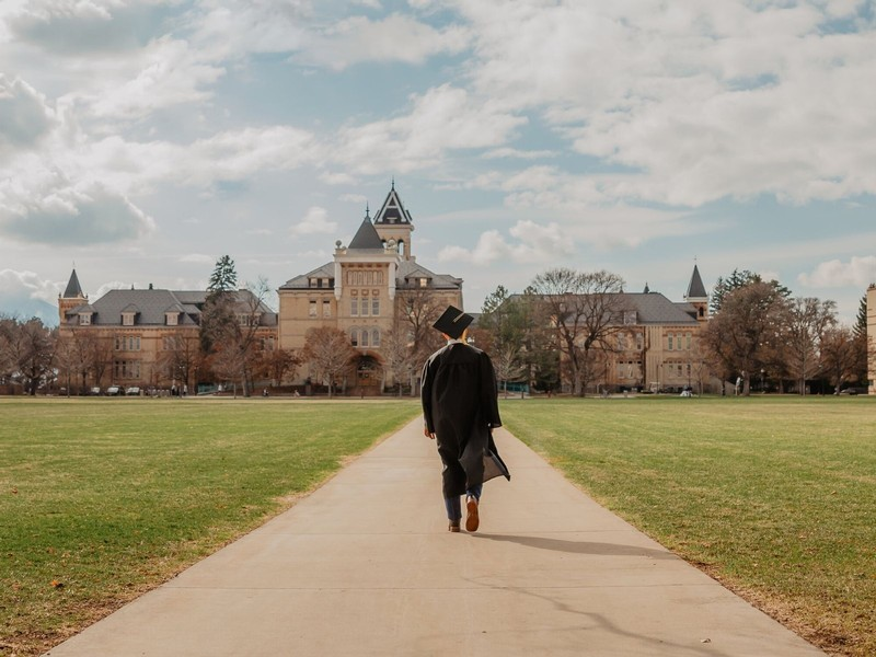 A USU graduate walks the sidewalk in front of Old Main