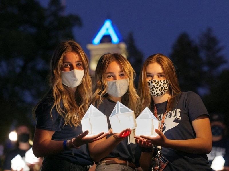 Three USU female students hold their lanterns at the annual Connections Week Luminary.