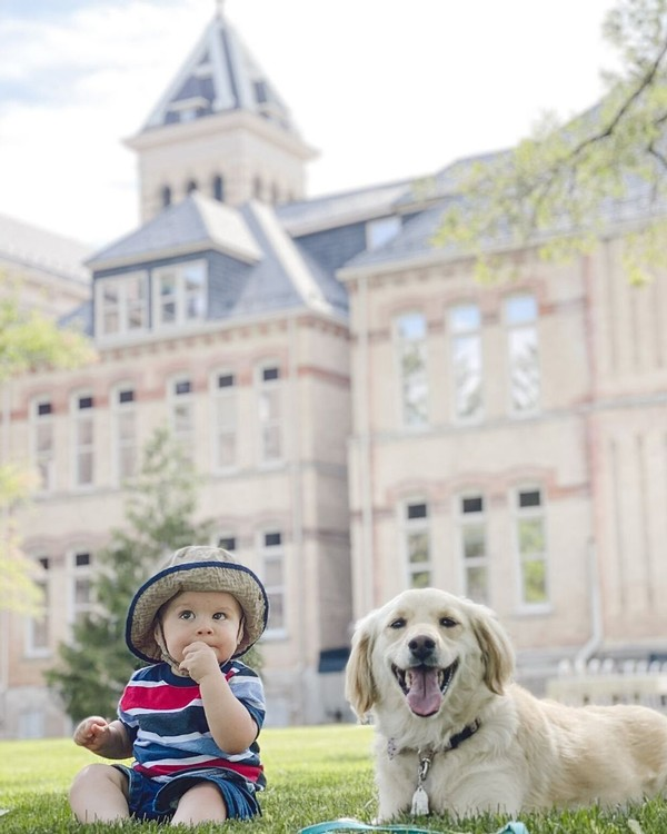 A baby and dog relax in the grass in front of Old Main.