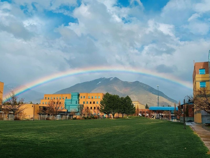 A large rainbow arches over the Logan campus