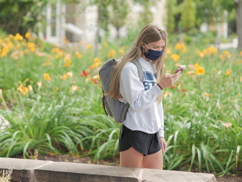 A student looks at her phone while walking on campus in her mask.