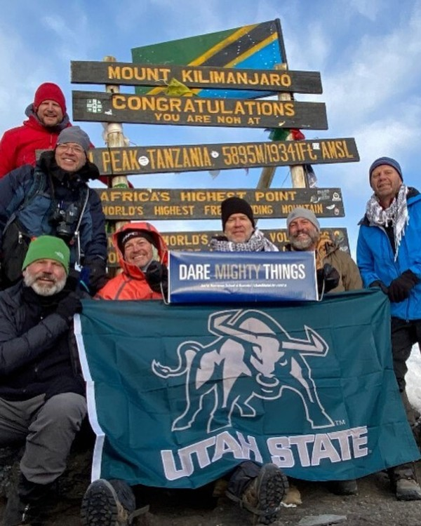 Aggies pose with a Utah State flag on top of Mount Kilimanjaro.