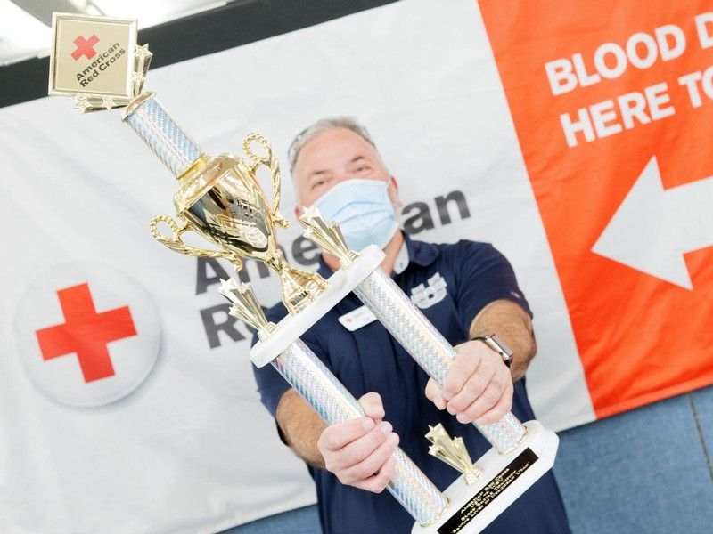 A male USU employee holds up a trophy