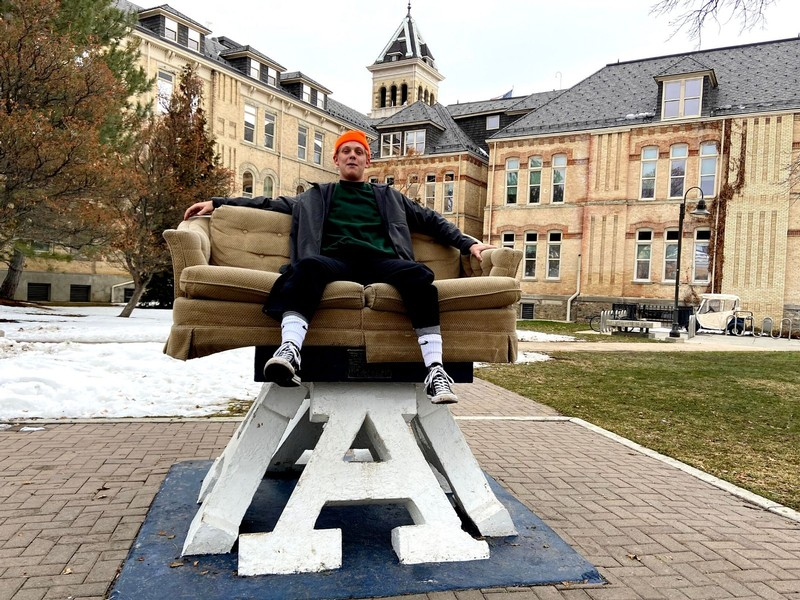 A male USU student sits on a loveseat atop the Block A at Old Main