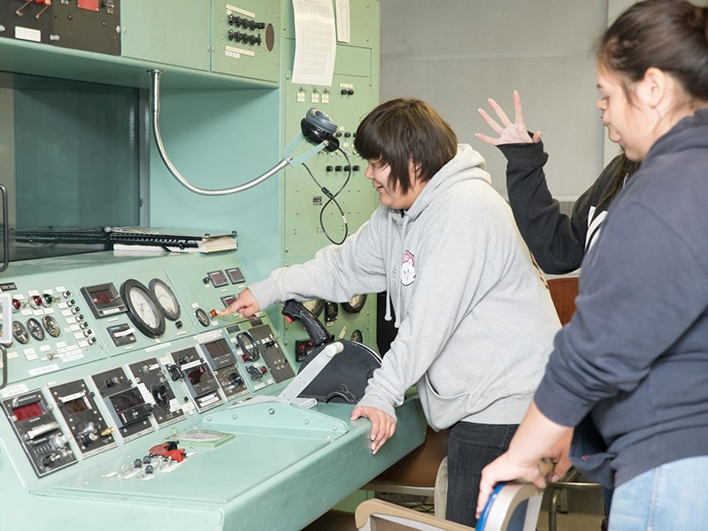 Ute Tribe students looking over an instrument panel