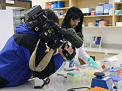 A USU graduate student and KSL camerman in the Institute for Antiviral Research lab