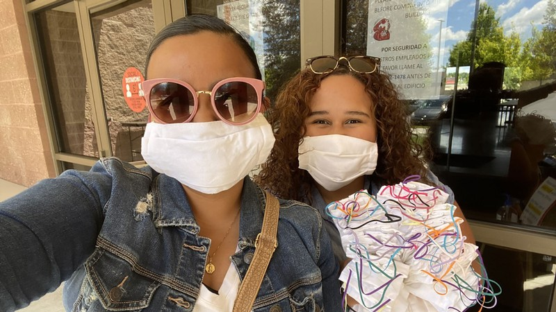 two women delivering masks to those in need.