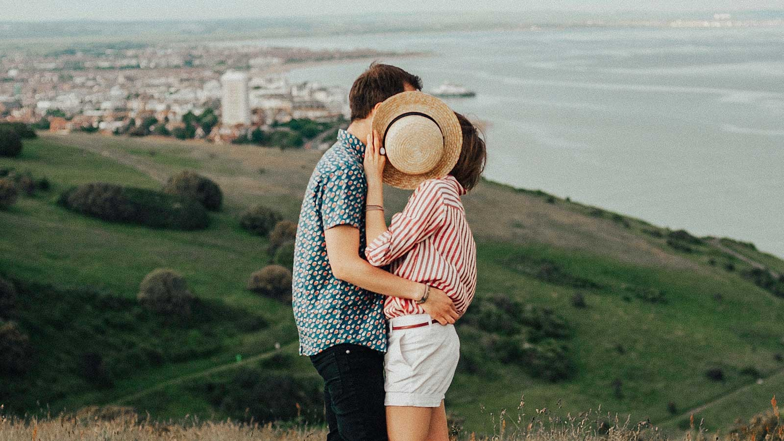 couple kissing in front of a city and coastal skyline.