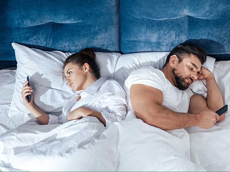 couple in bed on their mobile phones.