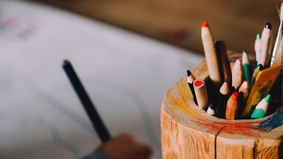 colored pencils in wooden jar on a desk.