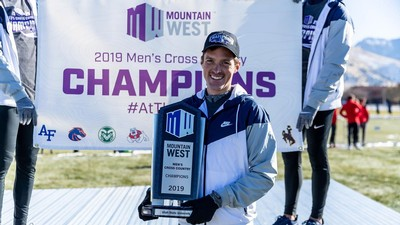 James Withers holds 2019 Mountain West Championship trophy.