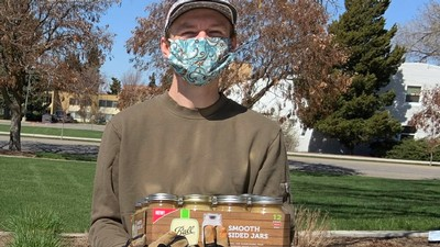 person in a mask carrying canned goods.