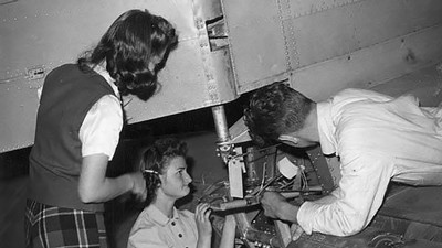 Two female and one male student working on the rear of an airplane, 1940s.