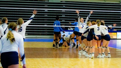 USU Eastern volleyball team celebrates on the court.