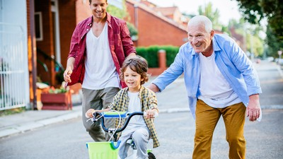 A father and grandfather help a young boy ride a bike.