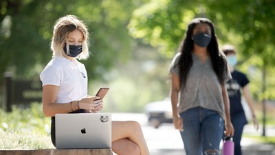 Student on a laptop and wearing a mask with students walking in the background, also wearing masks.