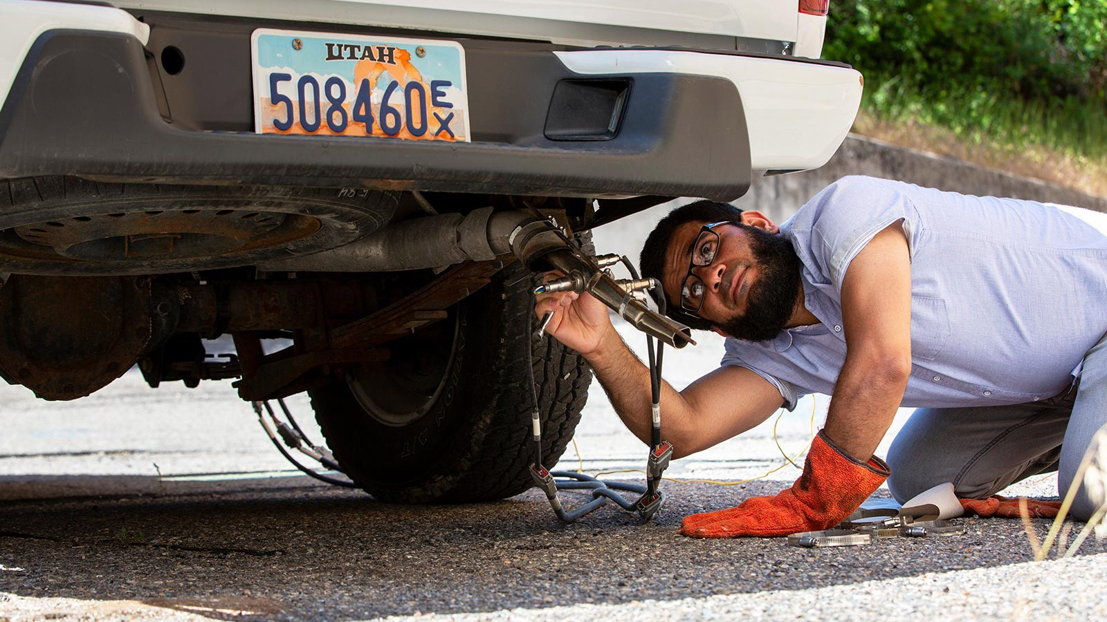 Motasem Abualqumboz checks the tailpipe of a truck.