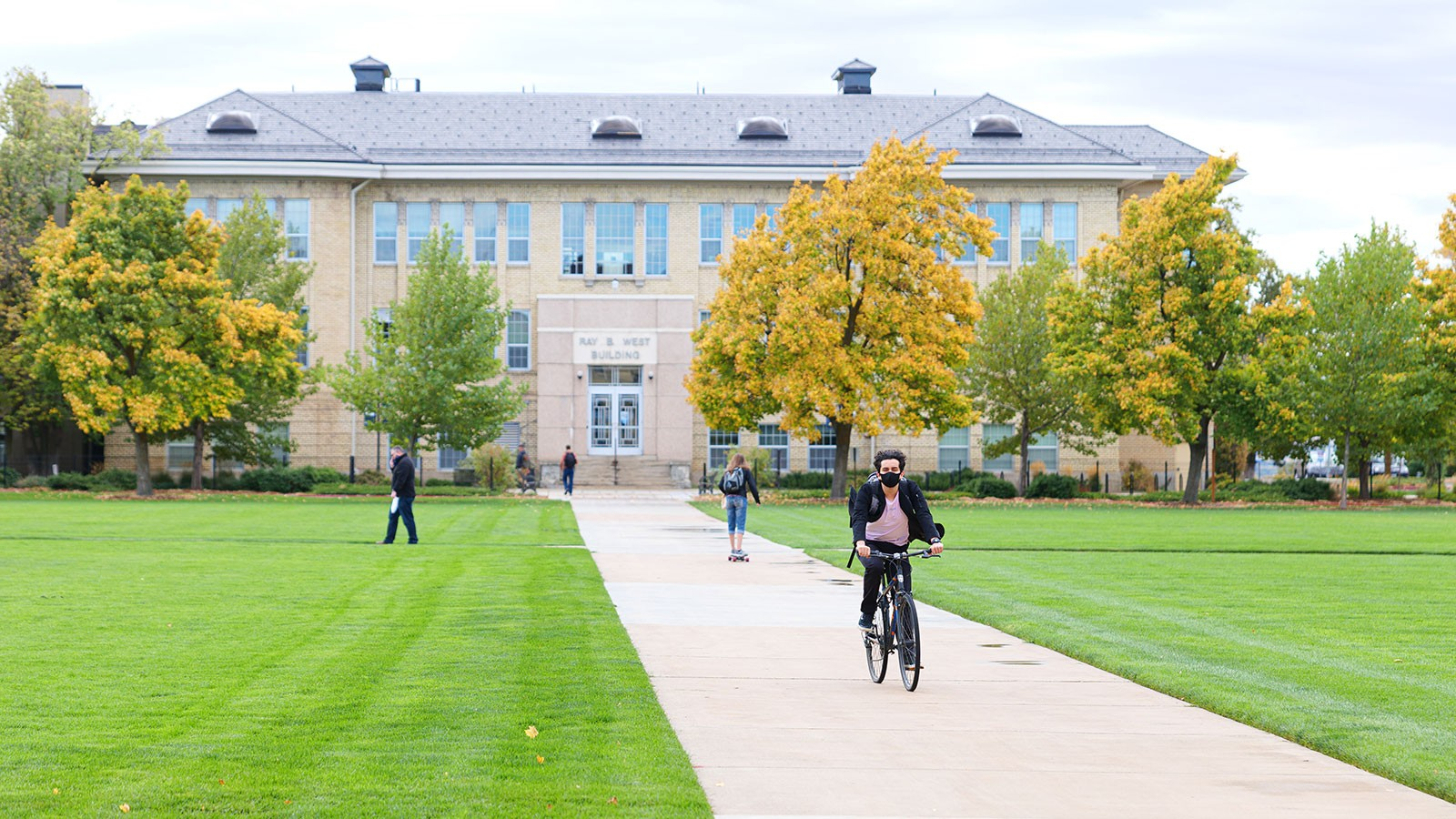 student riding a bike on the Quad near the Ray B. West building.