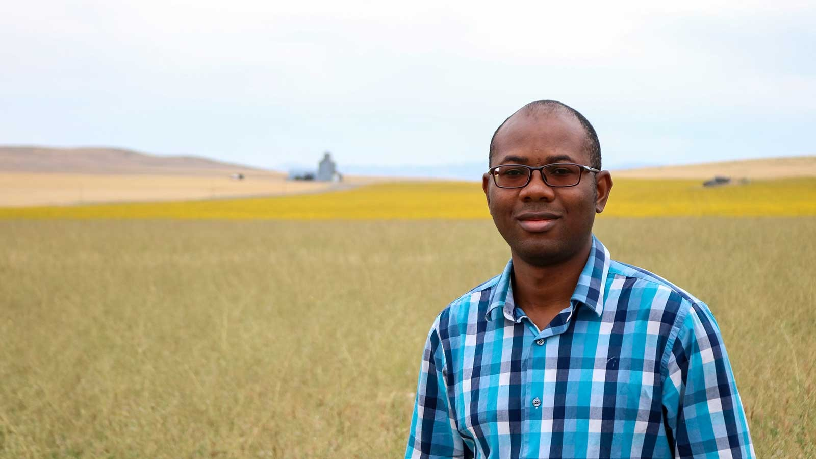 Idowu Atoloye poses for a photo in a field.