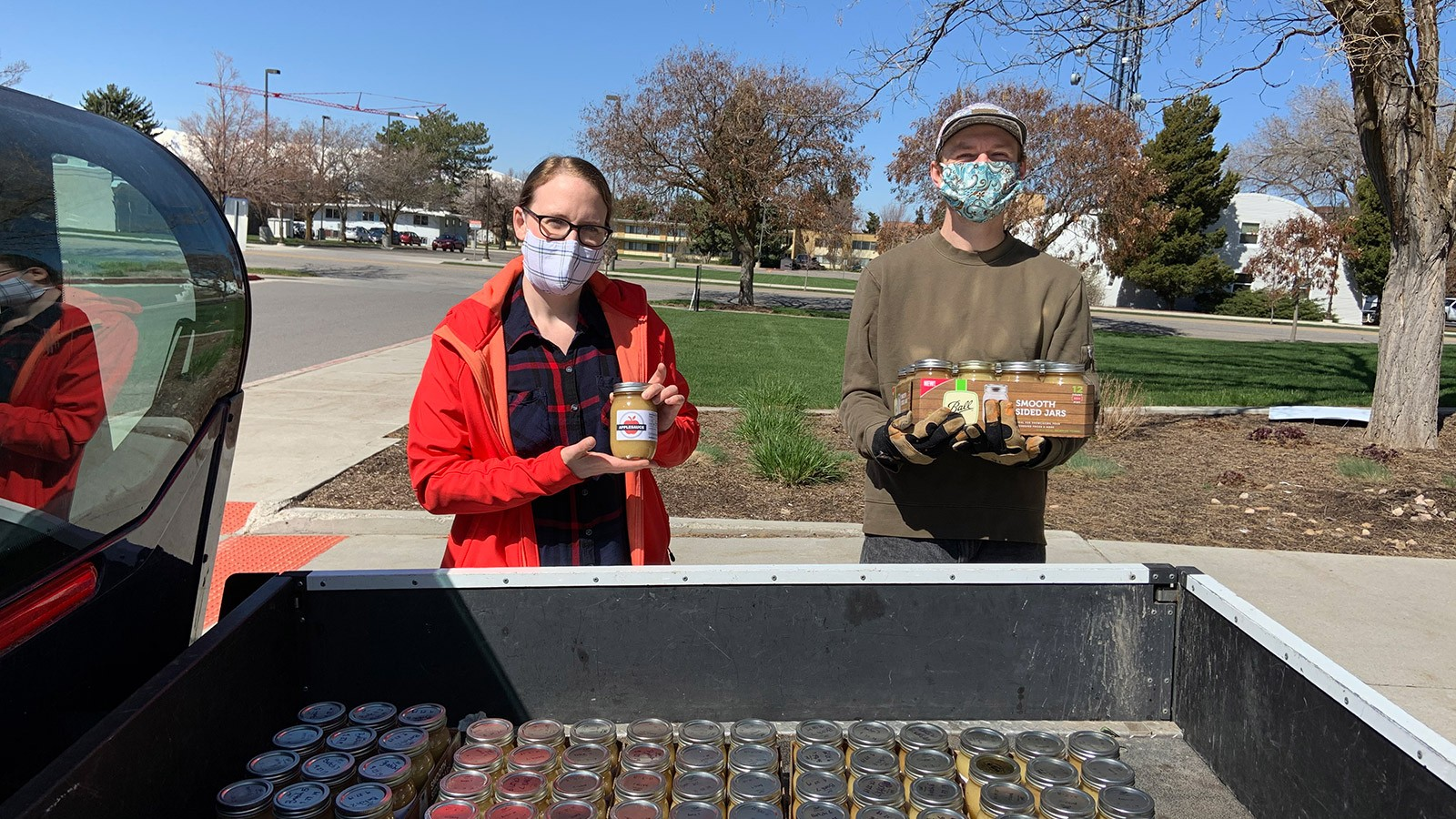 two students wearing masks loading canned food into a truck.