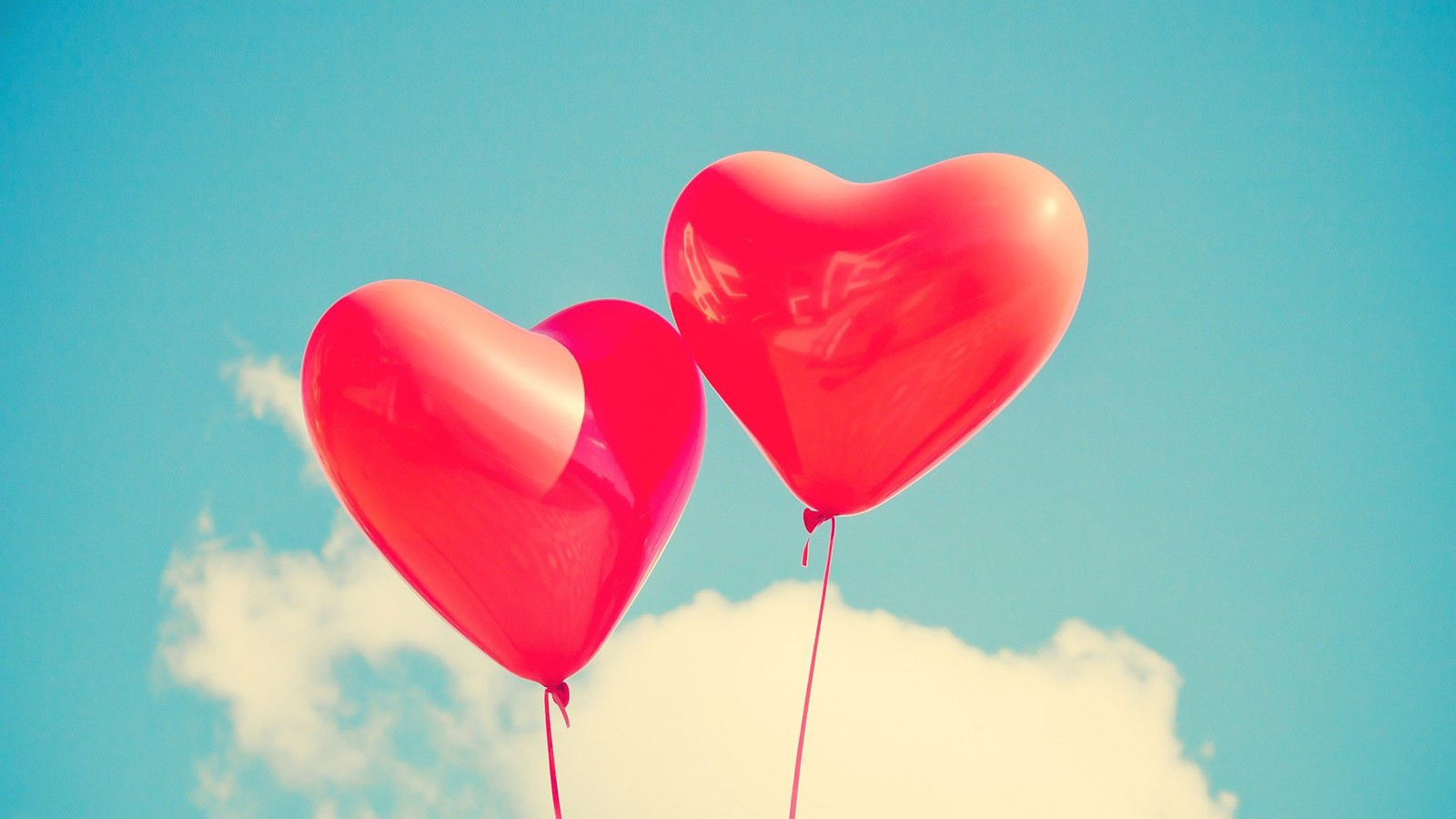 two heart-shaped balloons floating in the air.