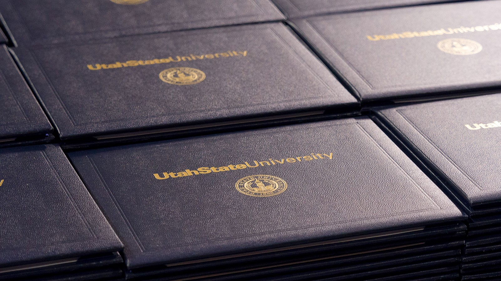 A set of stacked USU diploma covers.