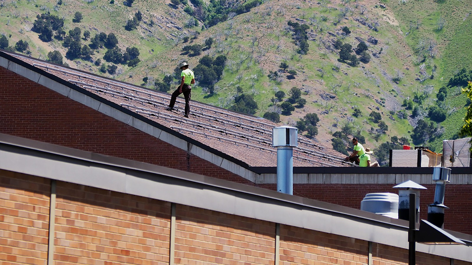 Construction workers installing solar panels on top of the fine arts visual building.