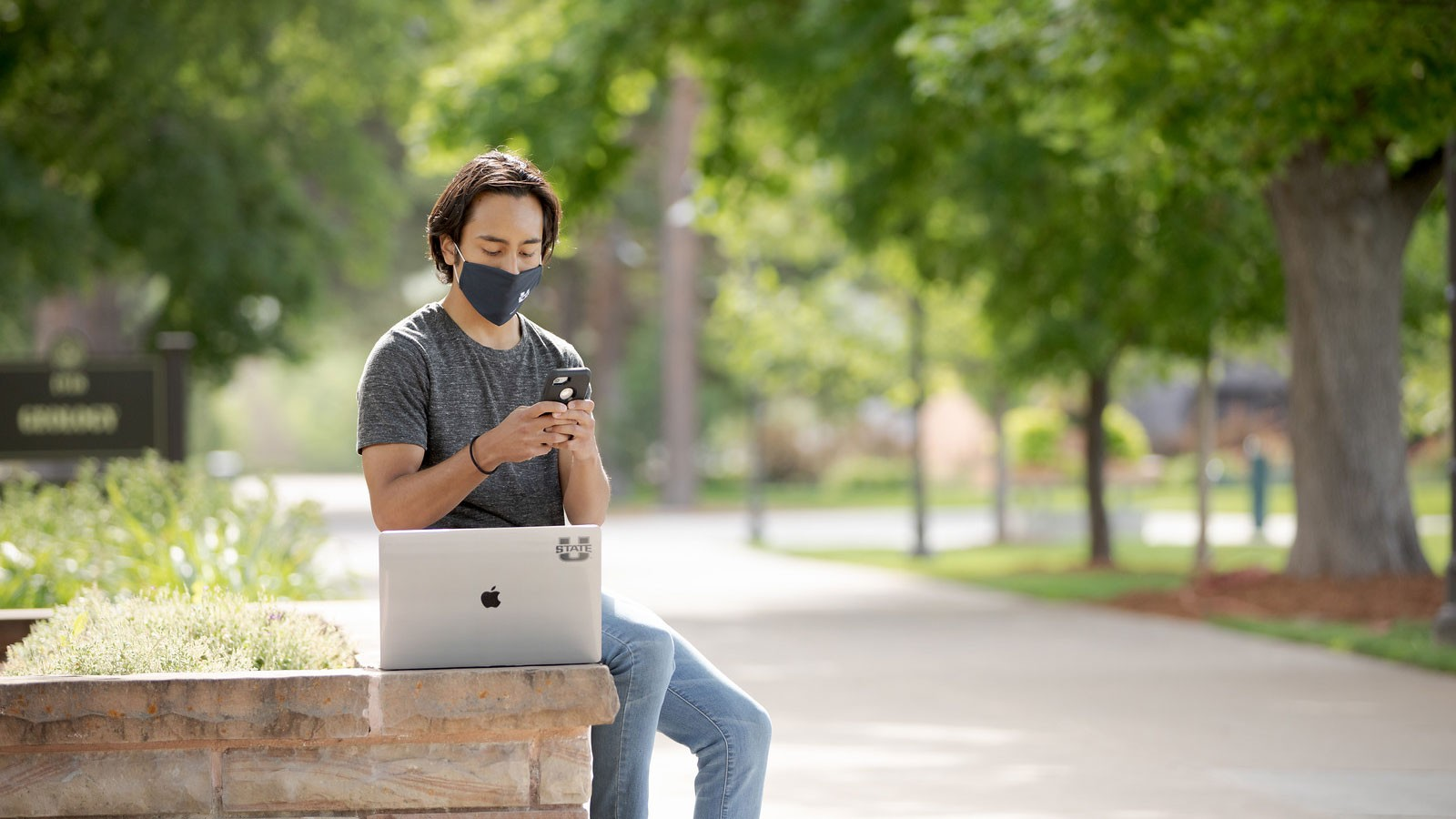 student wearing a mask and sitting next to a laptop.