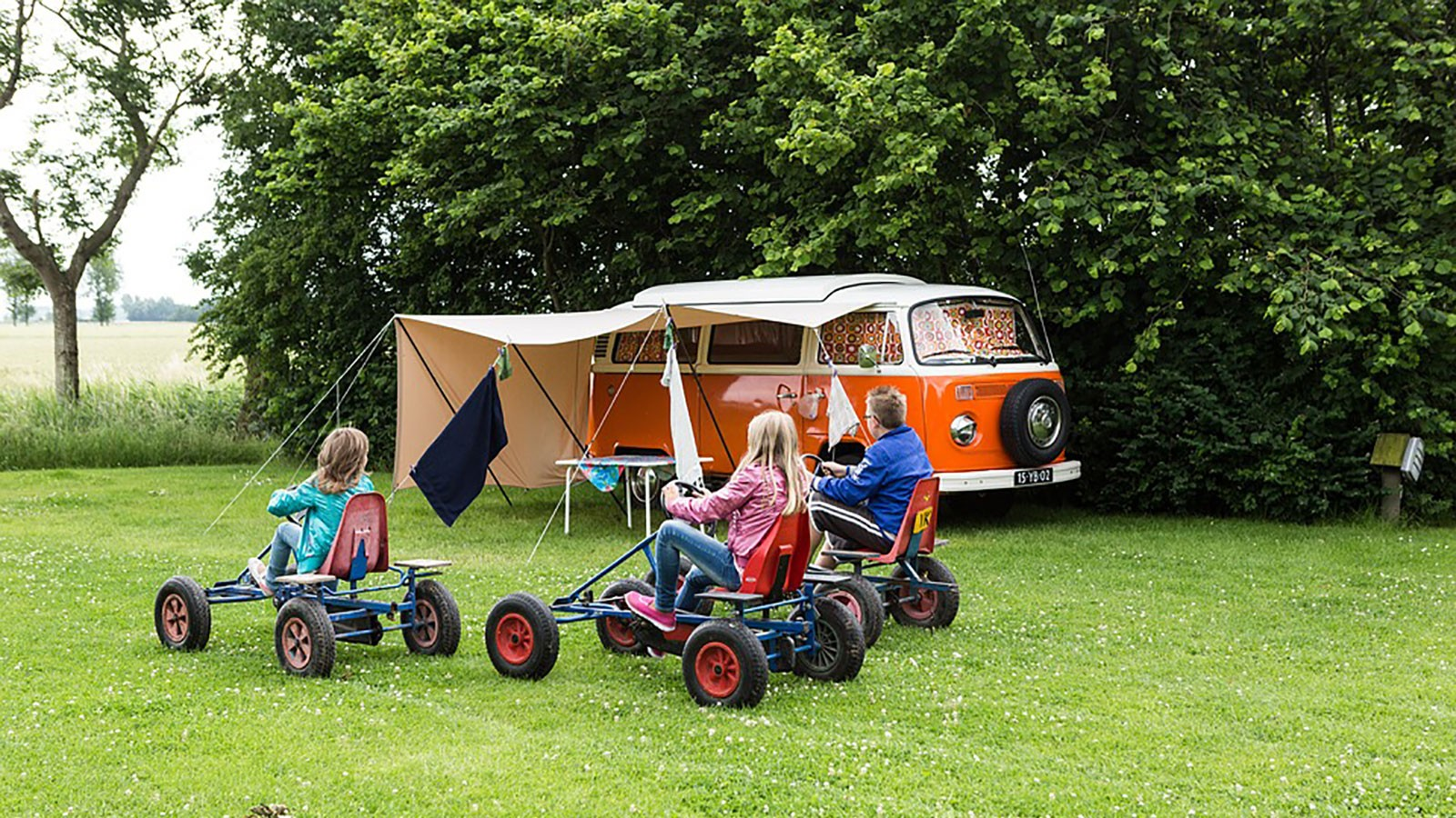 kids playing near a camper in a campground.