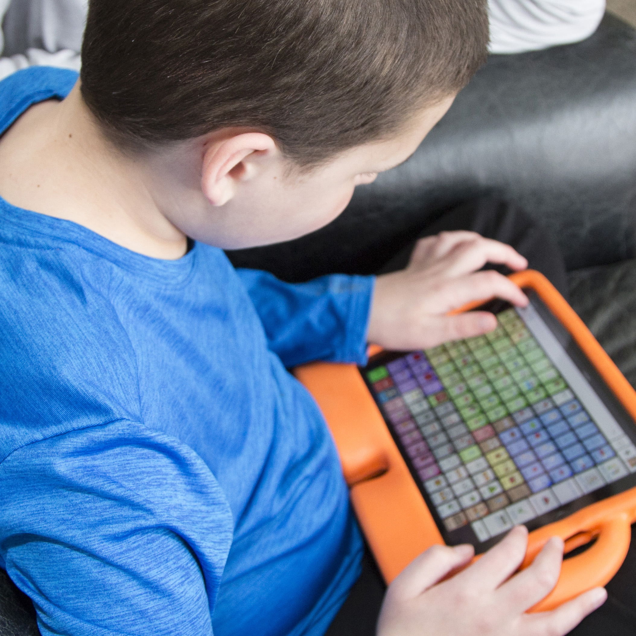 A boy uses an iPad communciation device