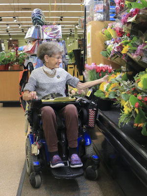 a woman in a wheelchair shops for flowers